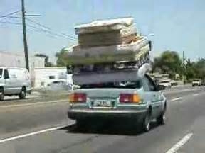 7 mattresses strapped to roof of car