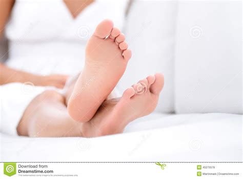 sit your y ass on that couch woman feet closeup barefoot woman relaxing sofa stock
