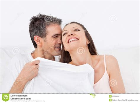 man and woman in bed man and woman cuddling in bed stock photography image