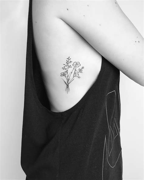 small black and white tattoo small minimalist wildflower with black lines