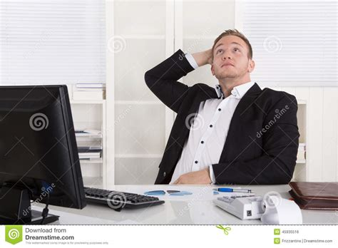 pensive dreaming businessman sitting at desk looking