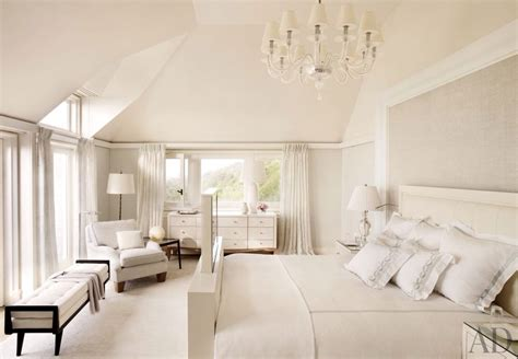 traditional master bedroom with clear glass chandelier high ceiling chair rail carpet