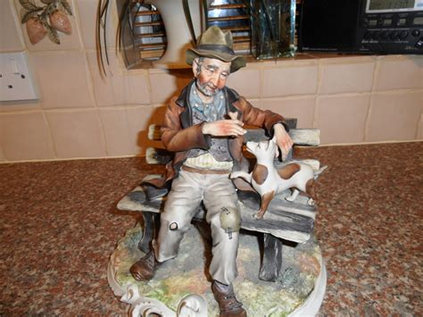 capodimonte man on bench i have capodimonte tr on bench holding a bone with a