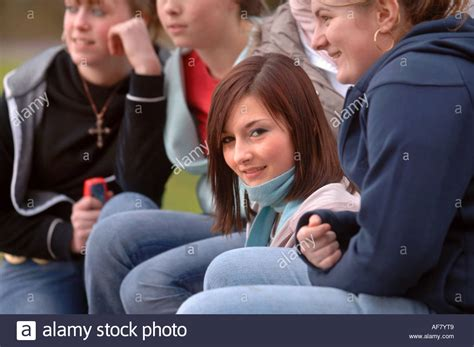 park bench group a group of teenage girls sitting on a park bench uk stock