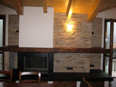 caminetti rivestiti in legno foto mansarda con camino e rivestimento parete in pietra