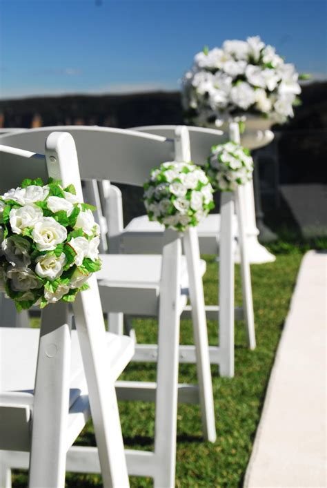 ailse chairs decorated with white silk flower balls