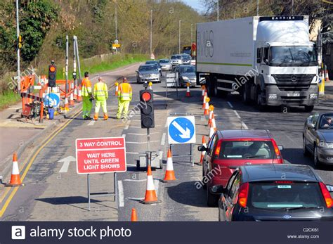temporary traffic lights at roadworks workmen at road works and temporary traffic lights stock