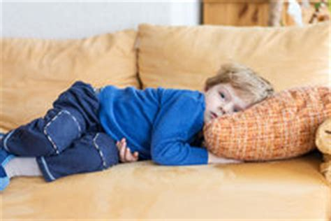 lying down on the couch tired toddler lying down with alarm clock in front stock