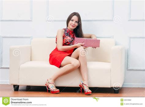 sitting in sofa a woman with gift is sitting on the sofa stock photo
