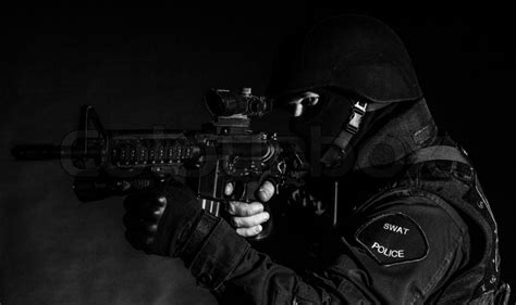 Swat White special weapons and tactics swat team officer on black background stock photo colourbox