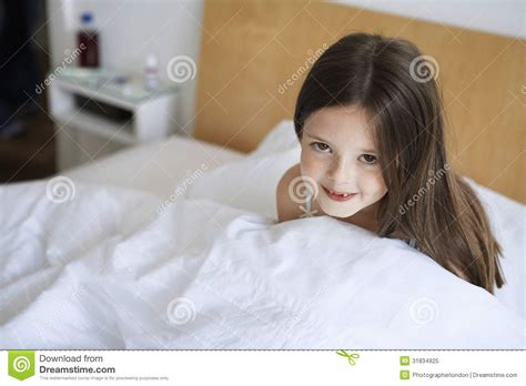 girl sitting on bed happy little girl sitting in bed royalty free stock photo image 31834925