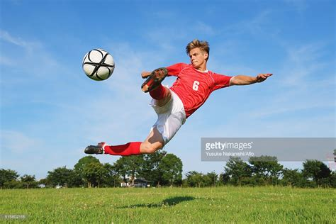 Kicking The soccer player kicking the in midair stock photo