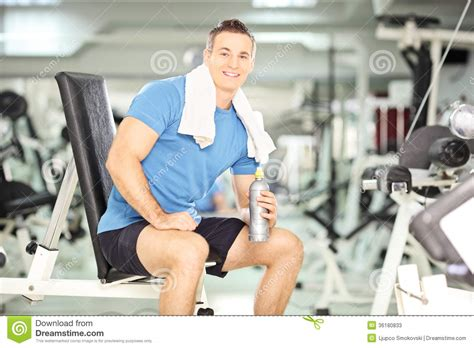bench drinking smiling man on a bench drinking water after exercise in