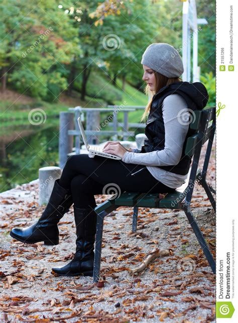 her bench woman sitting on a bench with her laptop royalty free