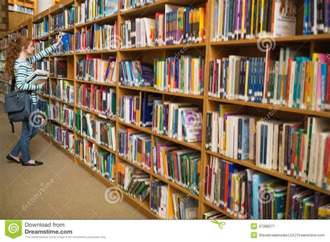 student taking a book from library bookshelf stock