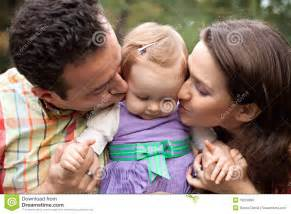 Kiss of love parents with their baby girl royalty free stock images