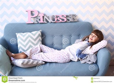 laid on the couch teenager girl lay on the sofa in pajama stock photo