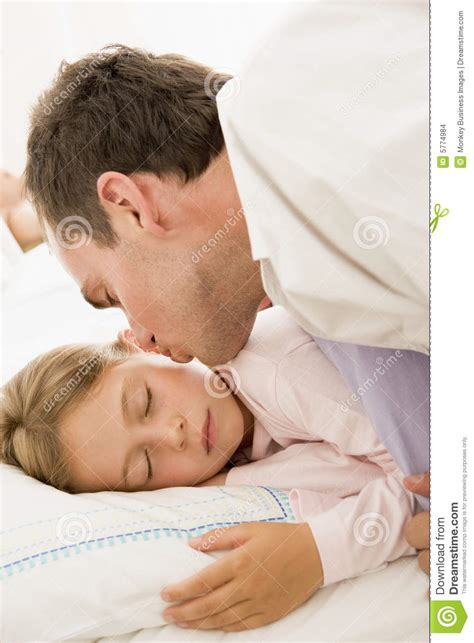 man waking young girl in bed with kiss stock photo image