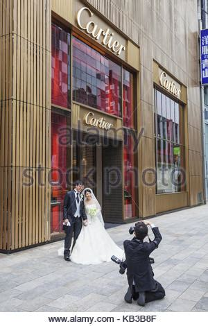 a wedding photographer poses the bride and groom outside