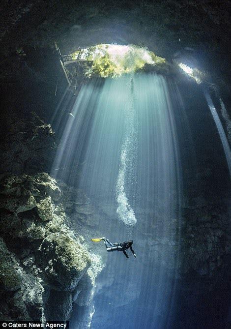 divers  pillars  sunlight  explore mexican caves