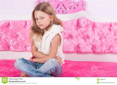 girl sitting on bed little girl sitting on a pink bed stock photos image