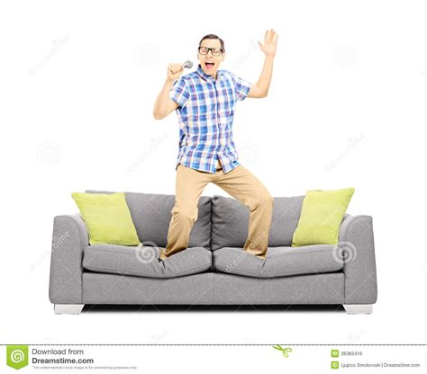 standing on the couch smiling guy with microphone singing and standing on a sofa