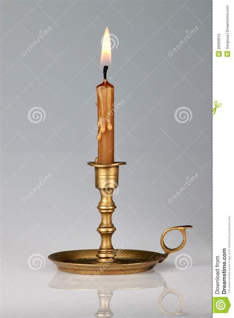 fashioned candle l lighted candle in an brass candlestick stock photo