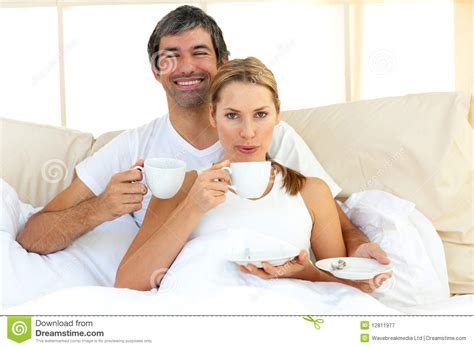 intimacy in the bedroom intimate couple drinking coffee lying in the bed royalty free stock photography