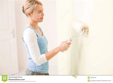 home improvement handywoman painting wall stock photo