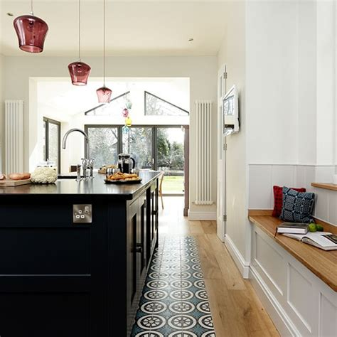 white kitchen with window seat and feature floor tiles