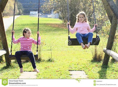 imagenes de niños jugando en un columpio two girls swinging on two swings royalty free stock