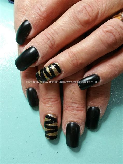 eye nails matte black with gold glitter and ribbon effect nail by