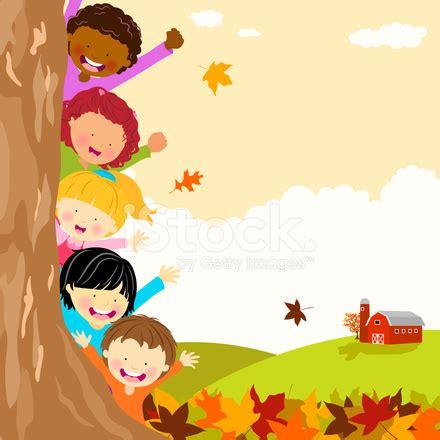 multi ethnic kids hiding behind tree at autumn stock