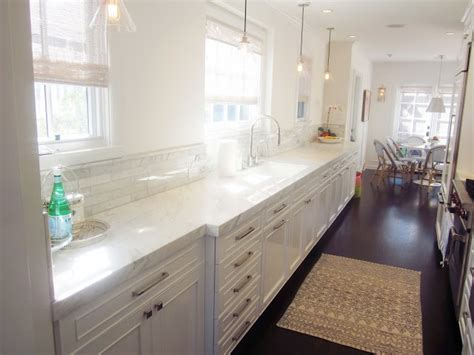 Galley Kitchen White Cabinets White On White Galley Kitchen Honed Marble Counters Calcutta Manhattan Marble Tile Backsplash