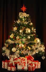 arbol de navidad lleno de regalos en la penumbra esperando