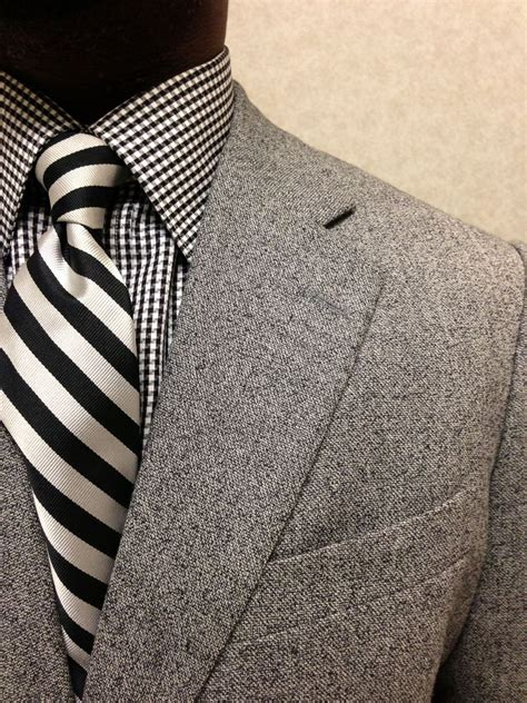 Pattern Shirt With Striped Tie | striped tie and checkered shirt beneath an elegant grey