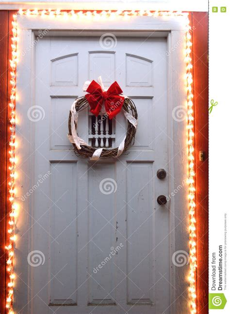christmas lights and wreath on front door at night stock
