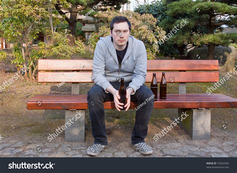 bench drinking a young man is sitting on a bench drinking beer stock