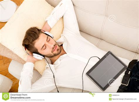 music on the couch young man listening to music on the couch mr yes pr no 0