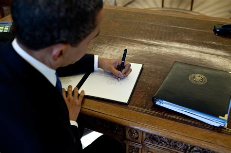 obama at desk file barack obama signs at his desk jpg wikimedia commons