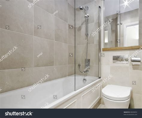 floor to ceiling bathroom tiles modern bathroom white ceramic appliances beige stock photo