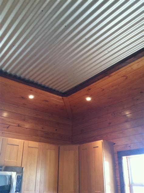 interesting tin ceiling framed by tounge and groove pine