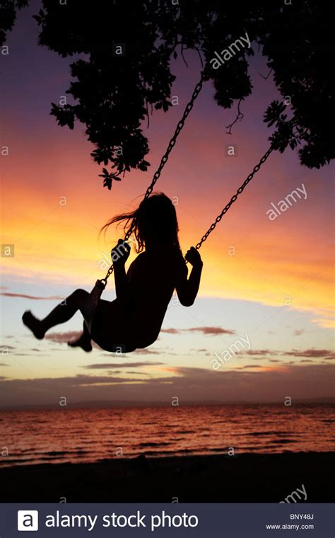 rope swing new zealand young girl on rope swing under pohutukawa tree at sunset