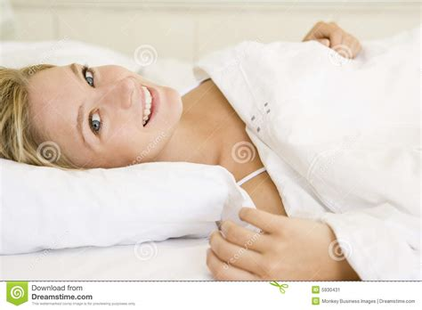 lying on bed woman lying in bed smiling stock image image 5930431