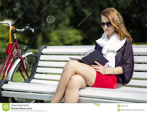 woman on bench woman sit on bench and read book stock photos image