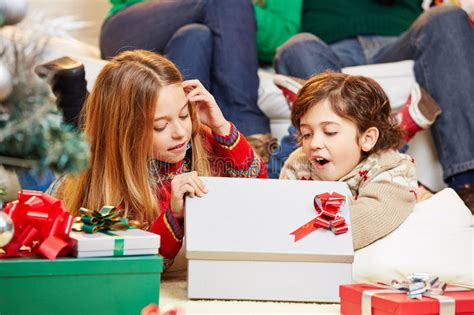Happy Children Opening Gifts Together At Christmas Stock ... Happy Kids Opening Christmas Presents