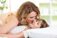 giochi si baciano nel letto lotta di solletico figlio della madre fotografia stock