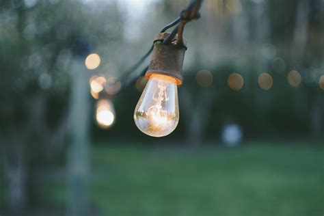 More And Less Lit by Light Bulb On A Wire Outdoors Photo By Nick De Partee