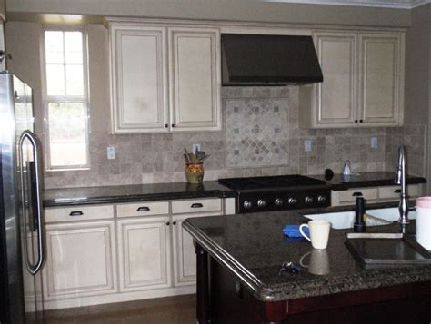 backsplash with white cabinets and black countertops