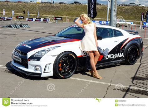 nissan sports car blue young beautiful woman posing next to the nissan gtr